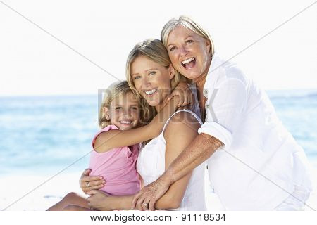 Grandmother With Daughter And Granddaughter Embracing On Beach Holiday