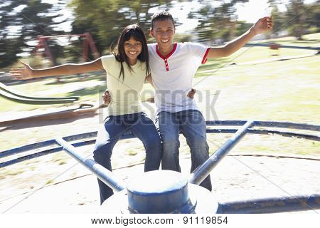 Teenage Couple Having Fun On Roundabout