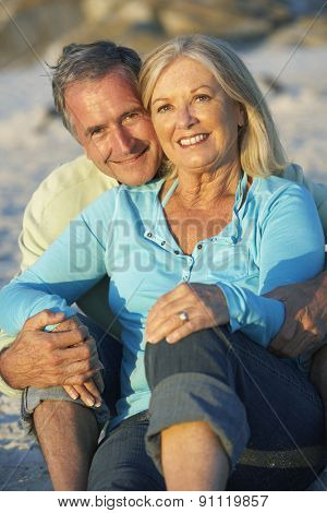 Senior Couple Relaxing On Beach Together In Evening