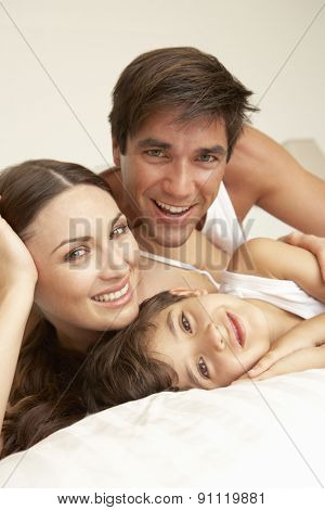 Young Family Relaxing On Bed