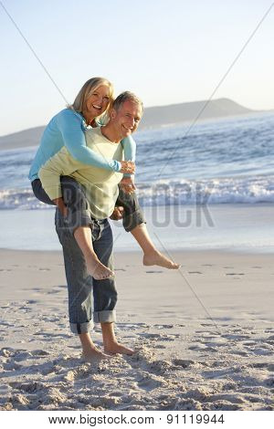 Senior Couple Having Piggy Bck On Sandy Beach