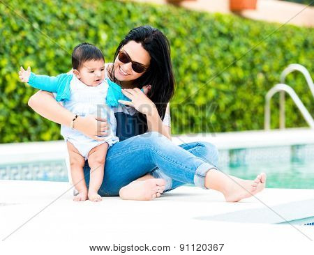 mother playing with baby boy near the swimming pool on a sunny summer day