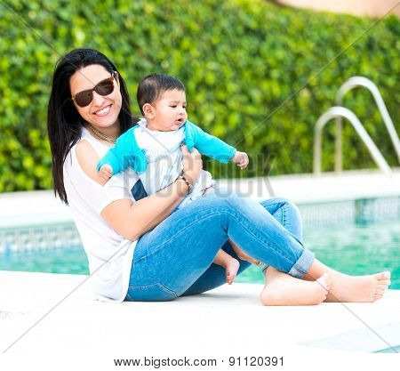 beautiful mother playing with baby boy near the swimming pool on a sunny summer day