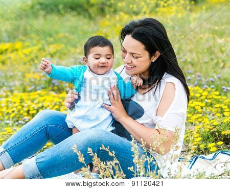 mother playing with her baby boy on the meadow in summer day