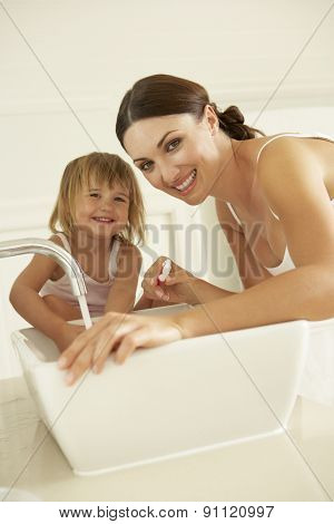 Mother And Daughter Brushing Teeth In Bathroom