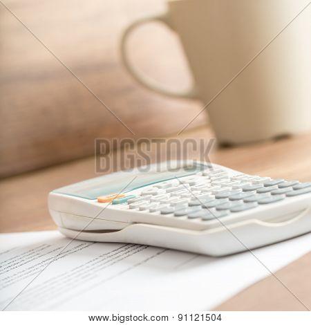 White Desk Calculator On A Document Next To A Mug