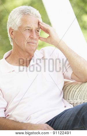 Depressed Senior Man Sitting In Chair