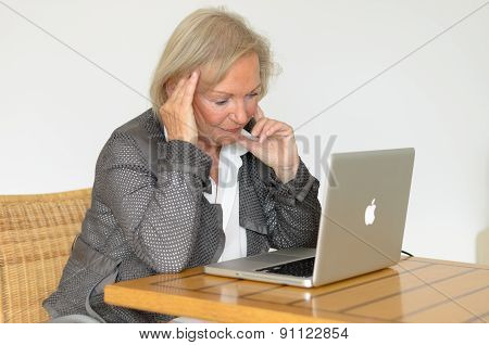 Active Blond Senior Woman In Front Of A Silver Laptop