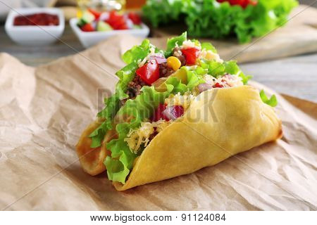 Tasty taco with vegetables on paper on table close up
