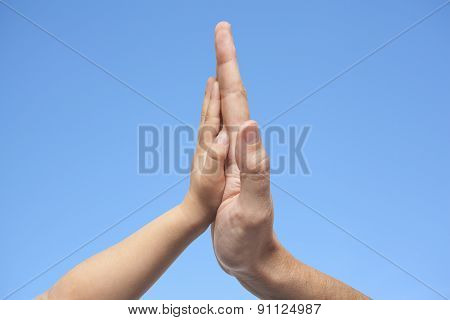 Father And Son In High Five Gesture On A Blue Sky Background