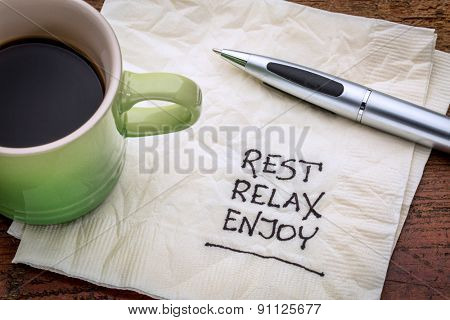 rest, relax, enjoy - handwriting on a napkin with a cup of coffee