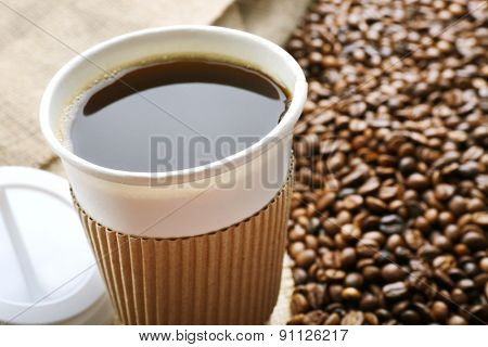 Paper cup of coffee with beans close up
