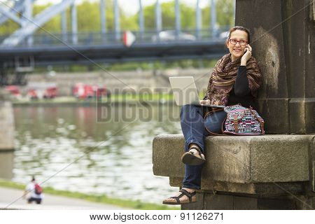 Young woman with laptop sitting on the embankment of the river in the old town talking on a cell phone.