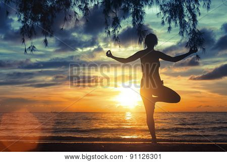 Silhouette of girl meditating on the sea beach during a wonderful sunset. Yoga and fitness.