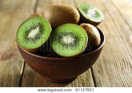Juicy kiwi fruit in bowl on wooden background