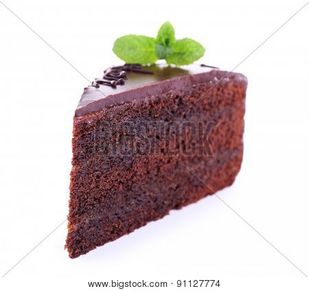 Piece of chocolate cake with mint isolated on white