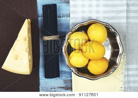 Cheese, black spaghetti and lemons on wooden table top view