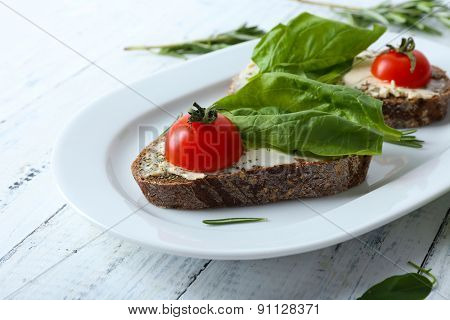 Delicious sandwiches with tomatoes and greens on plate table close up