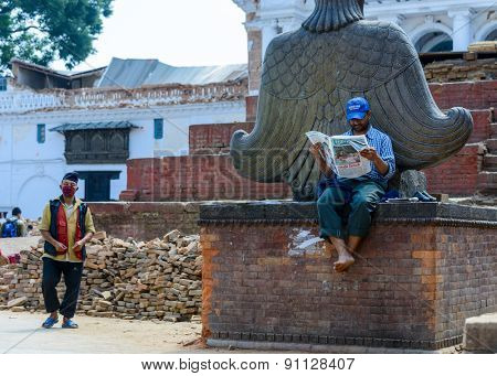 KATHMANDU, NEPAL - MAY 14, 2015: A man reads a newspaper on Durbar Square which was partially destroyed after two major earthquakes hit Nepal in the past weeks.