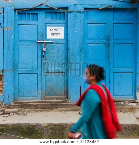 KATHMANDU, NEPAL - MAY 11, 2015: A woman walks past a danger sign on an old traditional house in Handigaun.