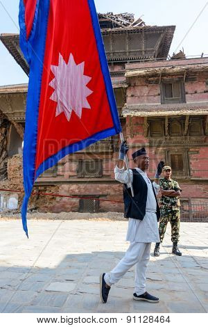 KATHMANDU, NEPAL - MAY 14, 2015: A man carries a large Nepal flag on Durbar Square, a UNESCO World Heritage Site.