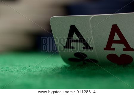 Two Aces On Green Table With Blurry Chips