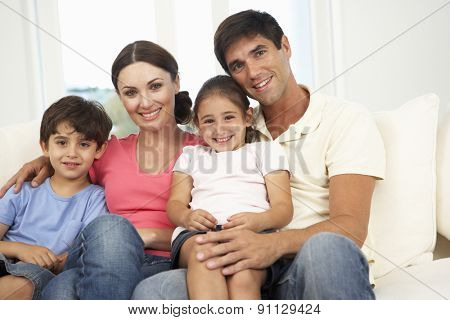 Family Relaxing On Sofa At Home Together