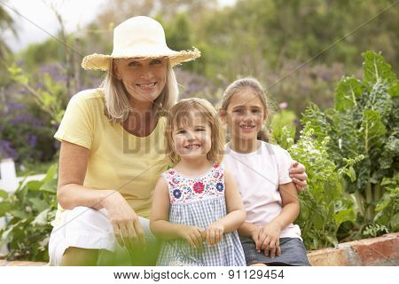Grandmother And Grandchildren Working In Vegetable Garden