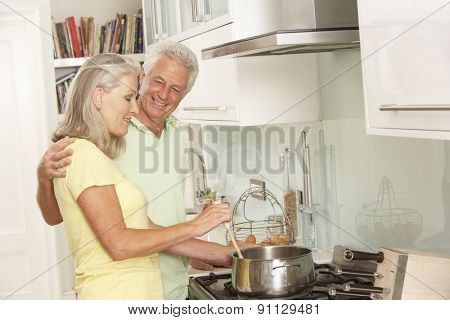 Senior Couple Preparing Meal At Cooker