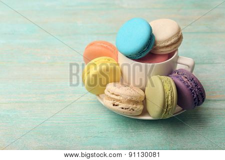 Tasty colorful macaroons on color wooden background