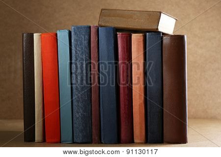 Old books on shelf, close-up, on dark wooden background