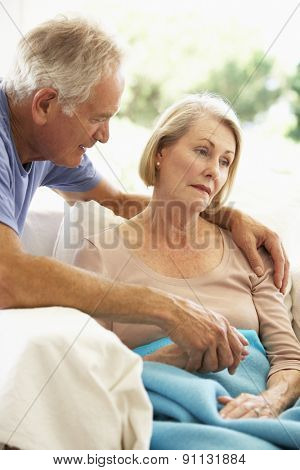 Husband Comforting Senior Woman Feeling Unwell Resting Under Blanket