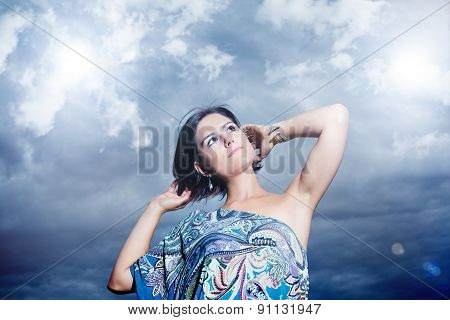 beautiful young woman on a background of sky and clouds