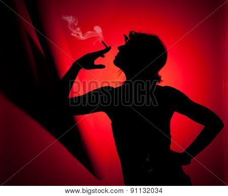 silhouette of woman smoking. Profile of woman pulling smoke on red background