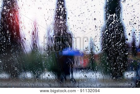 abstract image of falling rain drops through the window with city background