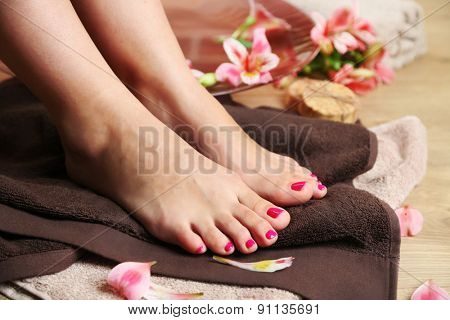 Beautiful female legs on  towel, on wooden floor background