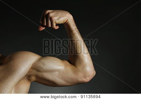Muscular arm flexing on dark background