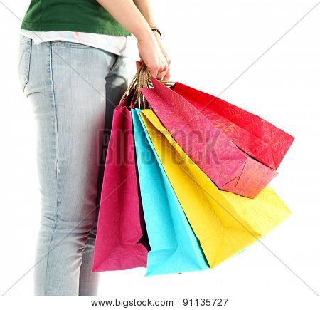 Colorful shopping paper bags in female hands isolated on white