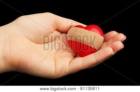 Female hand holding heart with plaster on black