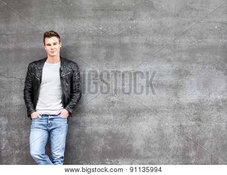 Casual young guy standing in front of concrete wall