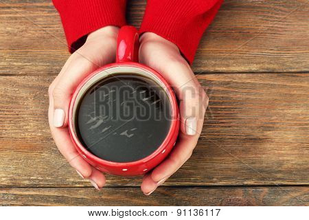 Female hands holding cup of coffee on wooden background