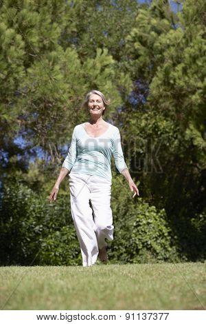 Senior Woman Running Through Summer Field