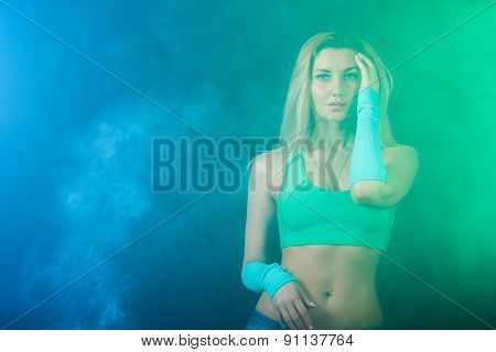 Beautiful Gymnast Between Blue And Green Clouds Of Smoke