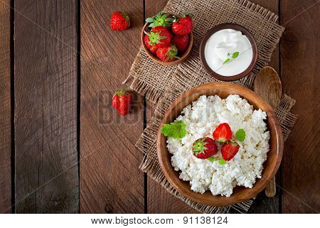 Cottage cheese with strawberries in a wooden bowl