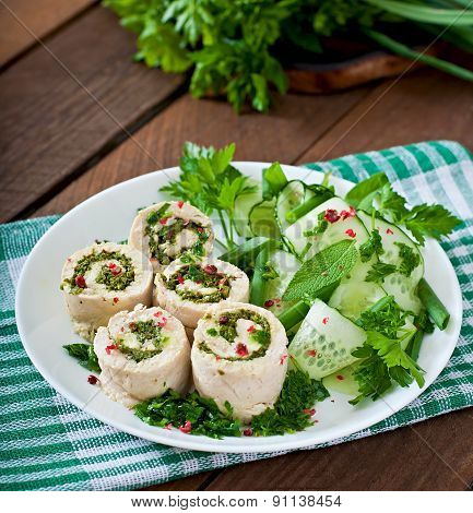Steamed chicken rolls with greens and fresh vegetable salad on a white plate