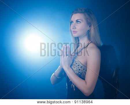 Woman With Dark Angel Wings Praying At The Background Of The Blue Light