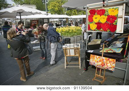 Tourists Take Photographs Of Each Other On Rembrandtplein Art Market In Centre Of Amsterdam