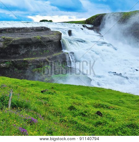 Powerful high-water waterfall in Iceland. For walks and observations on the hillside laid convenient path