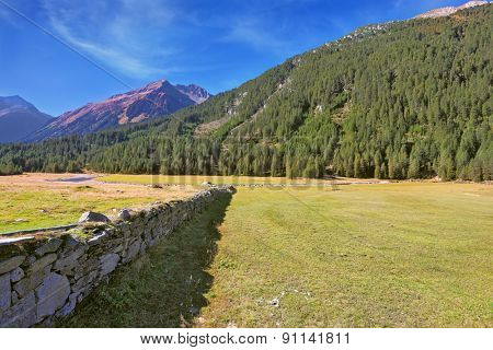 Scenic farm fields blocked by the stone fence. Shadow of the low fence beautifully lie on the grass. Alpine Valley in Austria. National Park Krimml