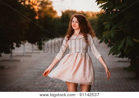 Beautiful Young Woman In A Pink Dress Posing In A  Garden